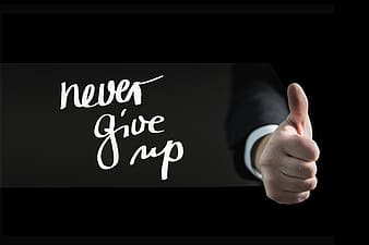 Human hand with never give up text overlay