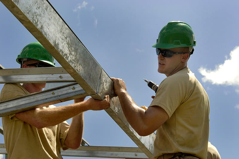 Man wearing beige shirt and green safety helmet holding white steel bars