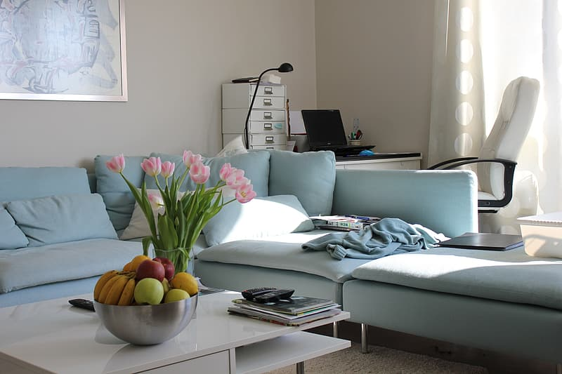 Grey sectional couch with flowers on center table