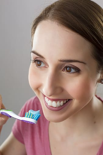 Woman holding toothbrush while smiling