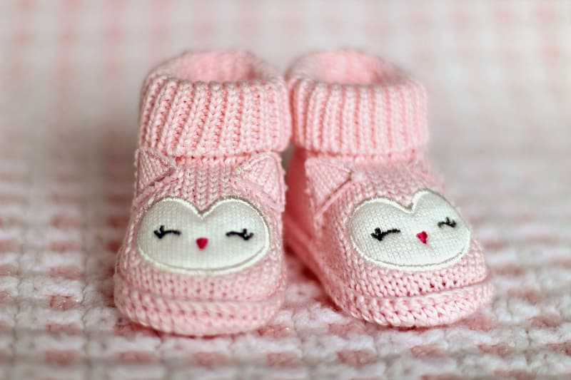 Shallow focus photography of pair of baby's pink knitted shoes