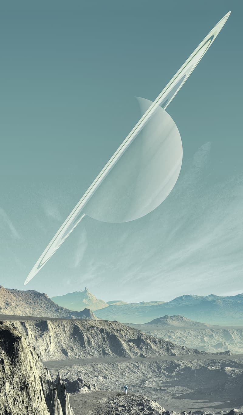 Ringed planet over brown mountains during daytime