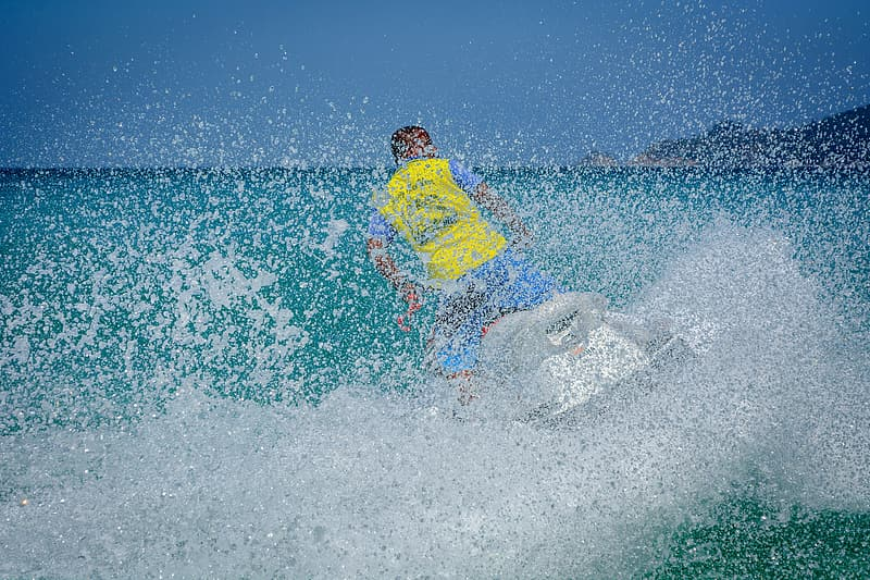 Man in yellow and blue riding personal watercraft