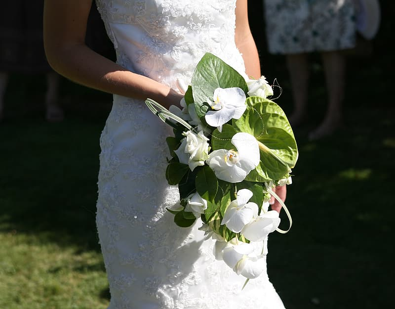 Woman wearing white floral wedding dress holding white flowers