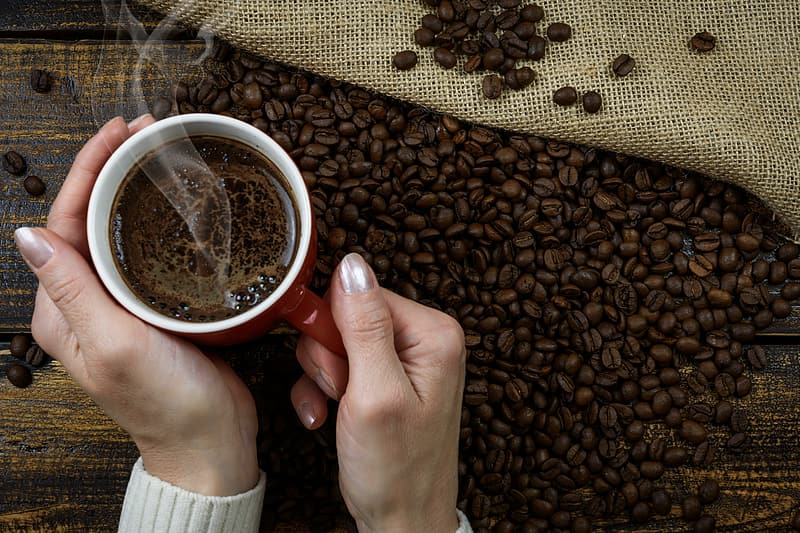 Person holding mug of coffee near on coffee beans
