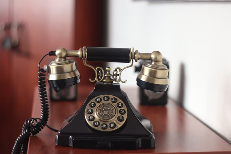 Black and gold rotary phone on red table
