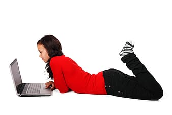 Woman laying in front of laptop computer