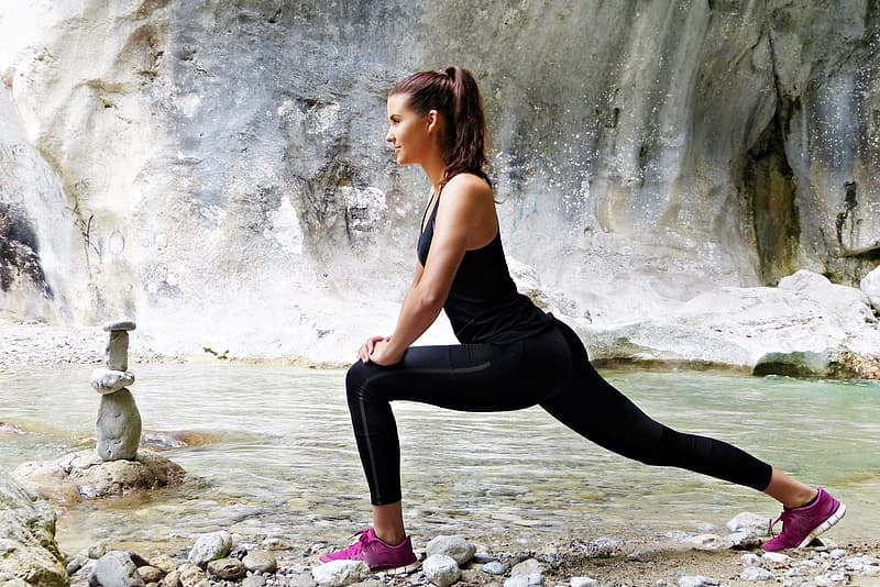 Woman wearing black track suit performing yoga near body of water