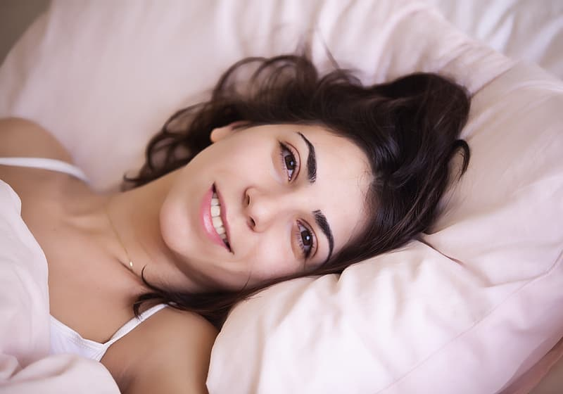 Woman lying on bed wearing white spaghetti-strap top