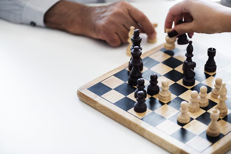 Two person playing chess on white surface
