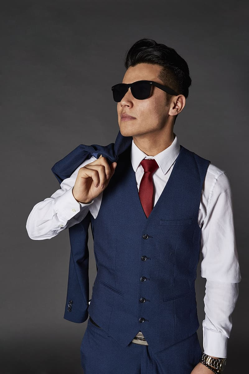 Woman in blue button-up vest and white dress shirt with brown necktie wearing black sunglasses
