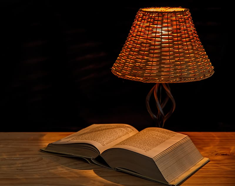Opened book on table near turned on table lamp
