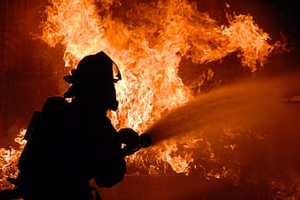 Silhouette of fireman putting out fire