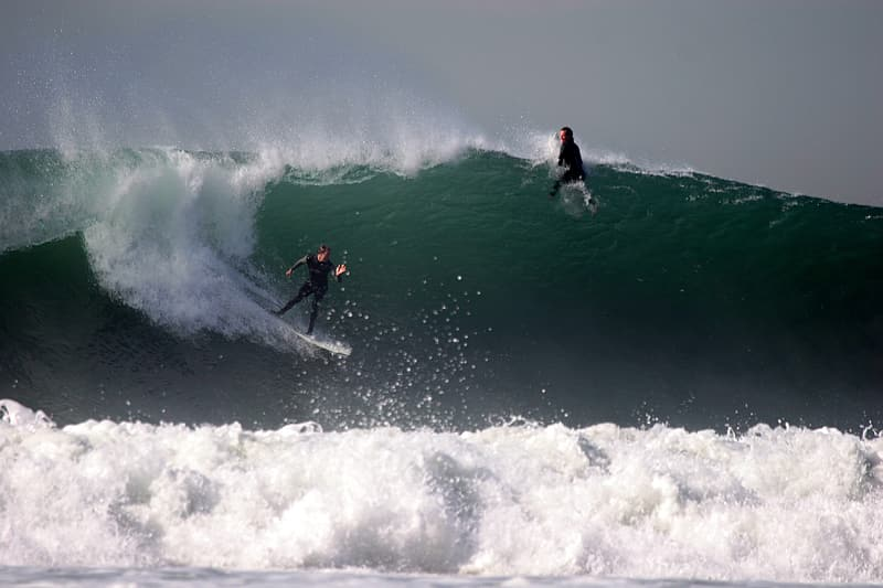 Two man surfing on big beach wave during daytime