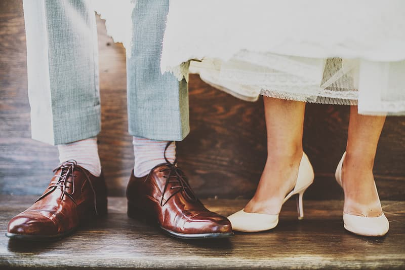 Person wearing pair of brown patent leather dress shoes and pari of white pumps
