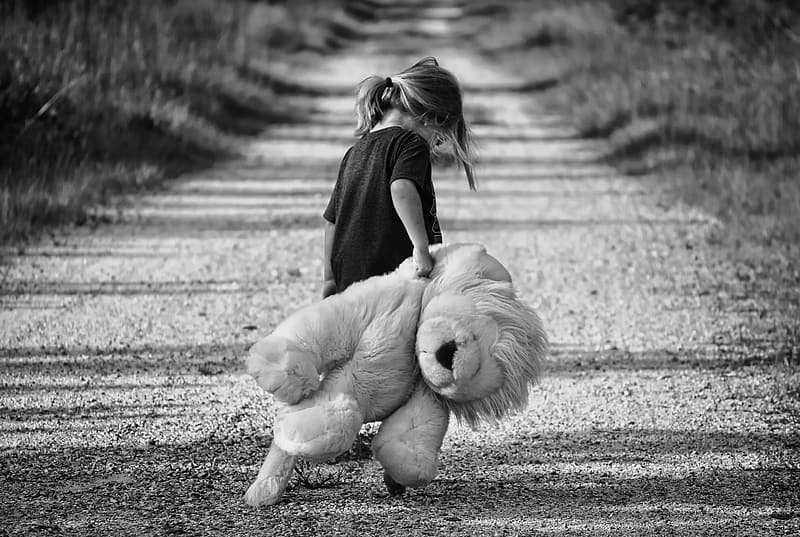 Girl in black crew-neck shirt holding lion plush toy in grascale photography