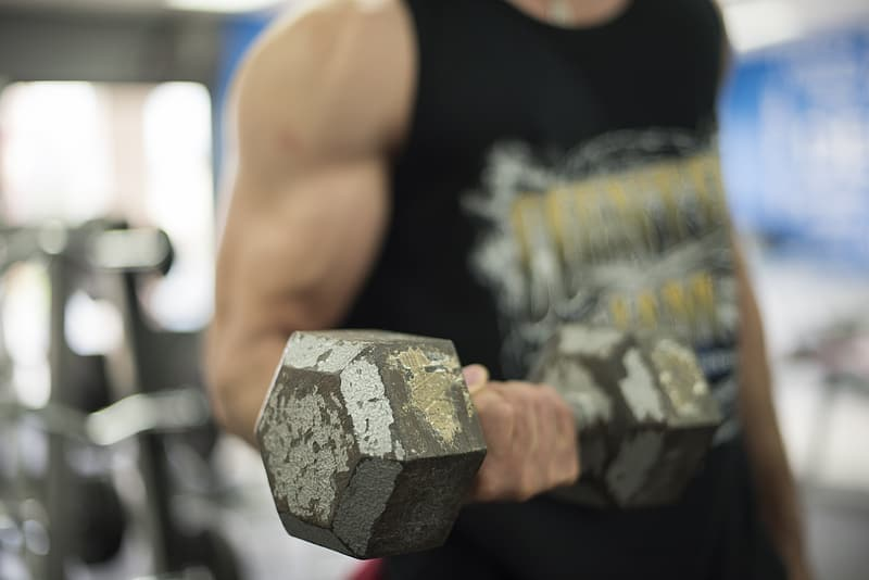 Man in black and grey tank top lifting a grey hex-type dumbbell with his right hand