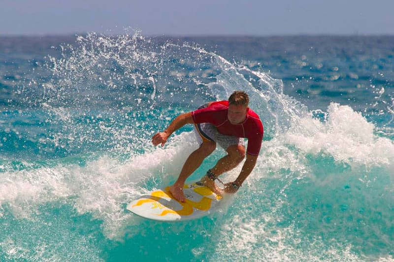 Man riding on surfboard during daytime