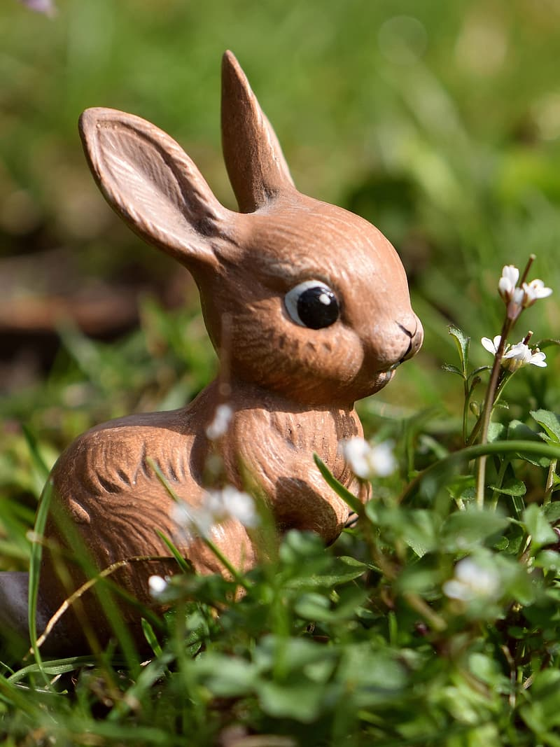 Brown rabbit figurine on green grass