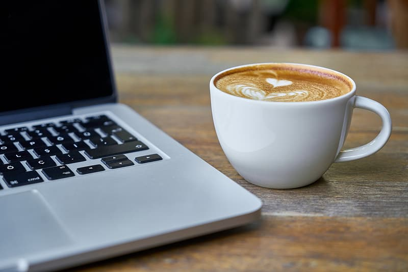 Brown and white coffee in white ceramic mug beside of gray laptop computer