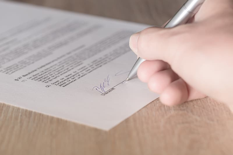 Person holding pen while signing in printing paper