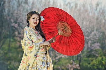 Woman in beige floral dress holding oil paper umbrella