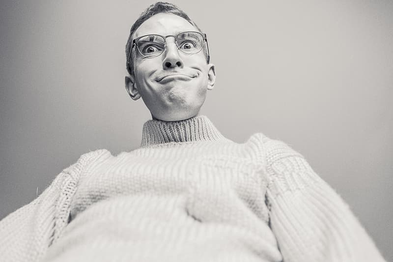 Grayscale photo of man wearing knit sweater and eyeglasses