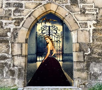 Woman in black dress standing in front of castle gate