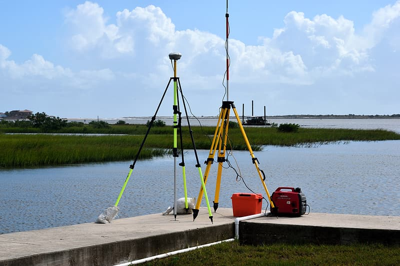 Two orange, black, and green tripods beside body of water