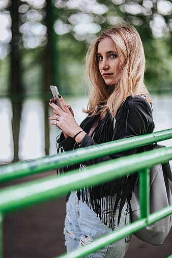 Woman in black long sleeve shirt holding smartphone