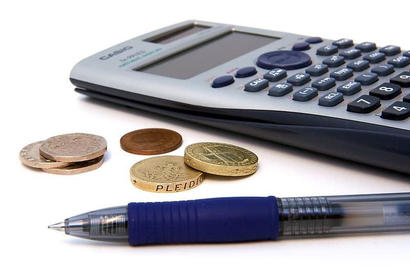 Gray and black calculator beside of blue ball pen and coins