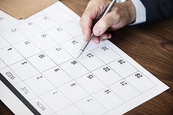 Person holding click pen writing on calendar