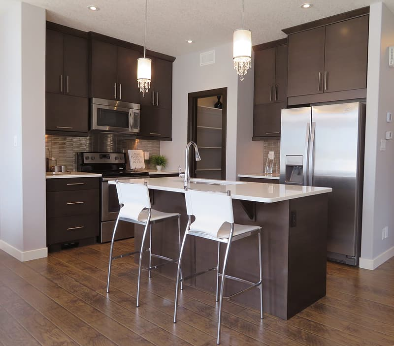 Two white and grey barstools beside kitchen island inside kitchen