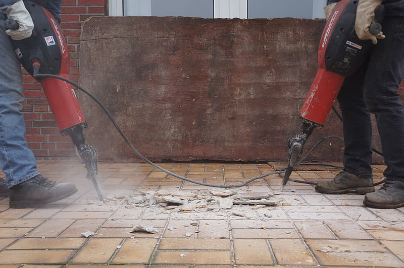 Two people drilling floor