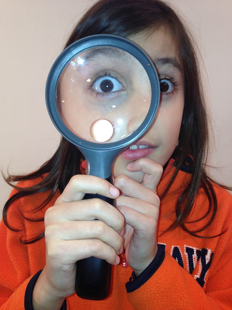 Woman in orange long sleeve shirt holding magnifying glass