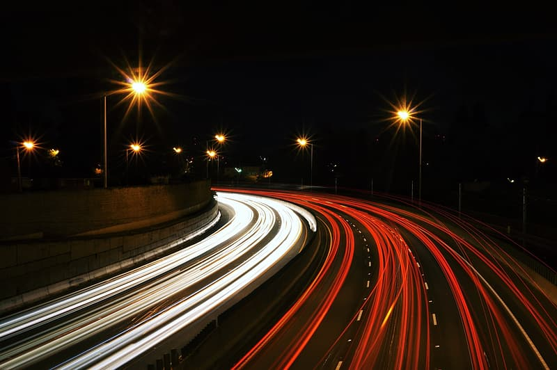 Time lapse photo of road with running vehicles during night time
