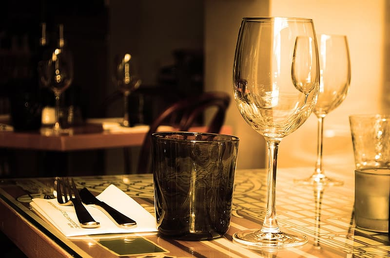 Two clear wine glass and black tinted drinking glass on table