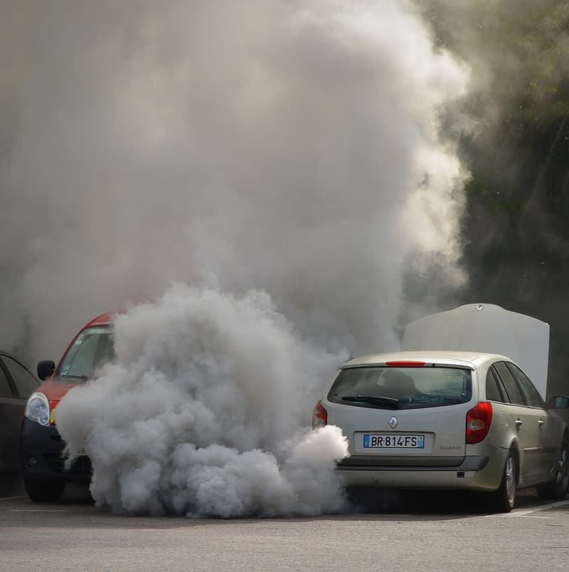 Vehicle blowing smoke on parking area beside red car