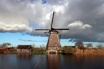 Windmill near body of water under cloudy sky during daytime