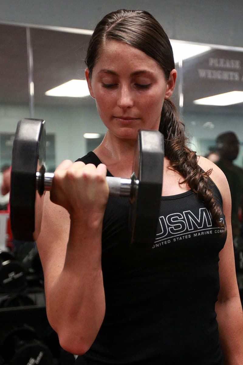 Woman in black tank top carrying dumbbell