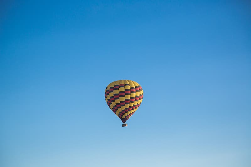 Yellow, red, and black hot air balloon flying under blue sky