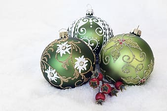 Three green Christmas baubles on white surface