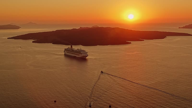 Cruise ship on body of water during sunset