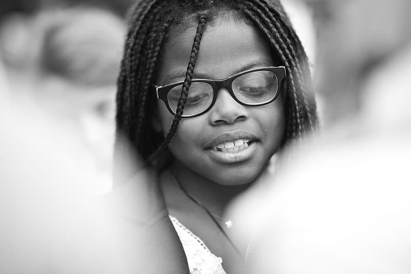 Grayscale photography of smiling girl wearing eyeglasses