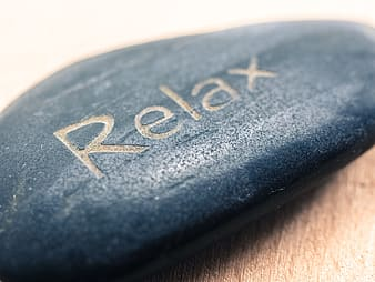 Closeup photo of blue stone with relax text engraved