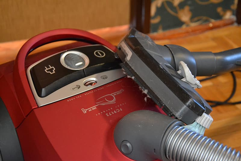 Red and silver canister vacuum cleaner on floor