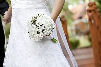 Person wearing white dress while holding white petaled flower bouquet