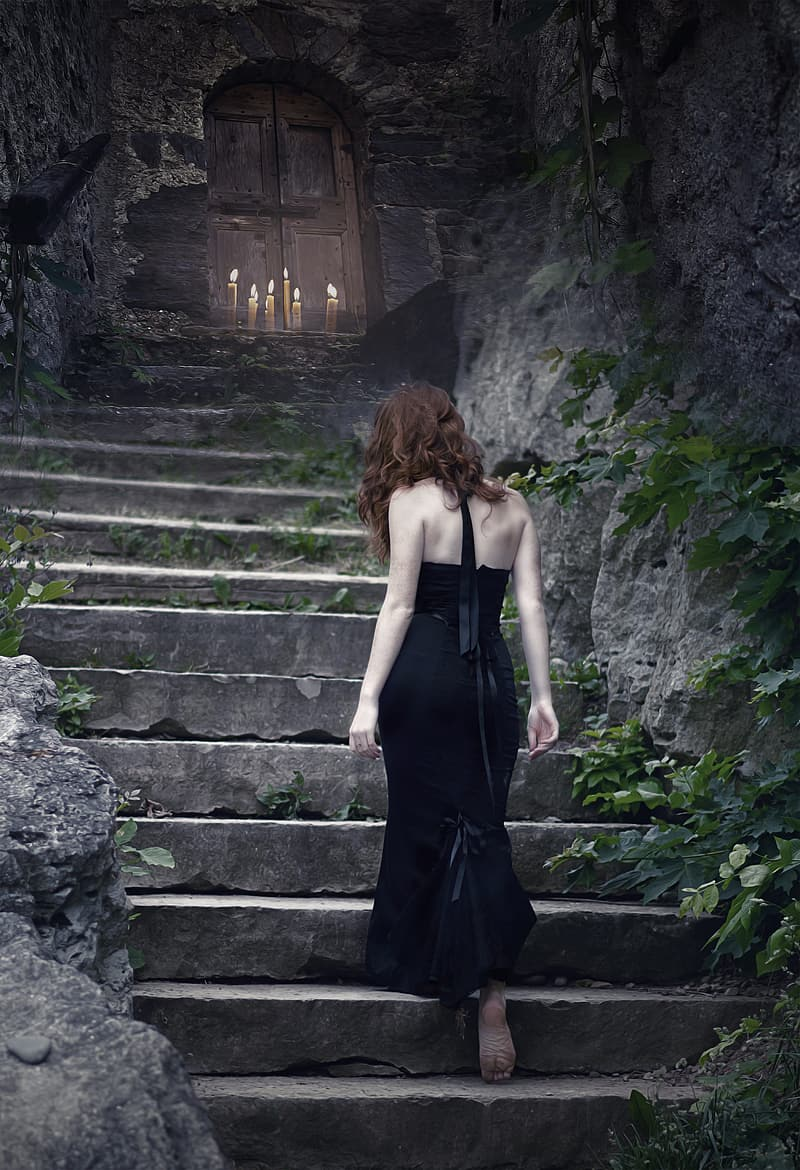 Woman in black spaghetti strap dress standing on stairs