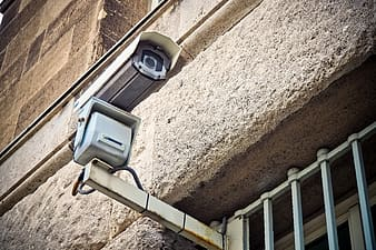 White bullet-type IP camera attached on gray grills