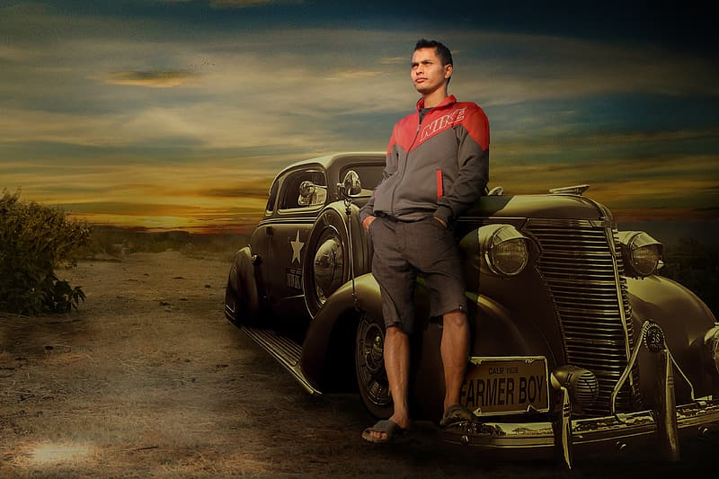 Man wearing red and black full-zip jacket and black shorts leaning on black car